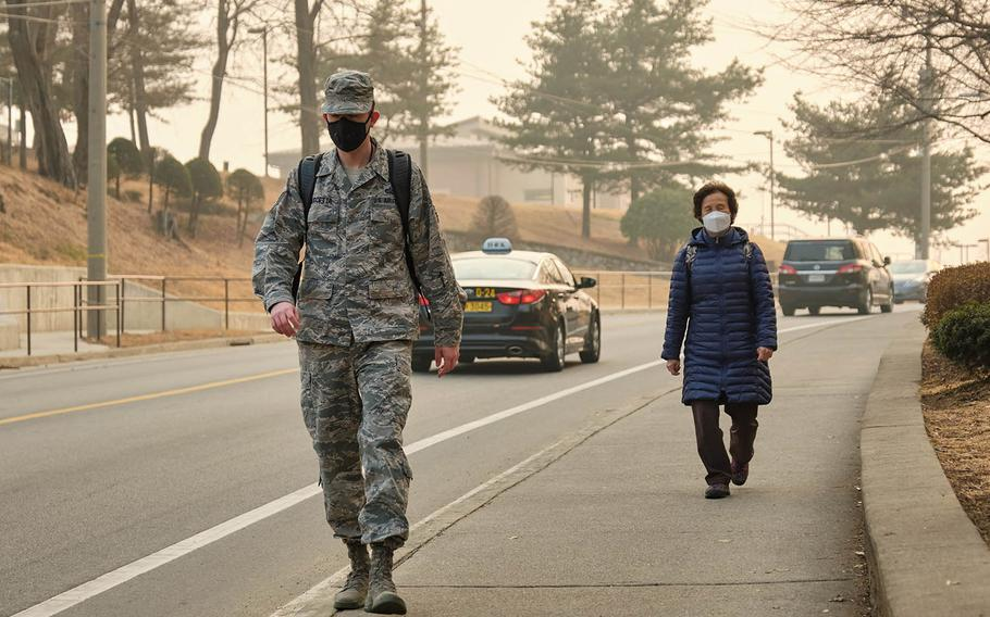 Pedestrians wear air-filtering masks at Osan Air Base, South Korea, March 6, 2019. Since 2017, the Air Force has permitted masks when pollution hit a certain level. But before a recent change, Army regulations had barred most soldiers from wearing filtering masks in uniform.