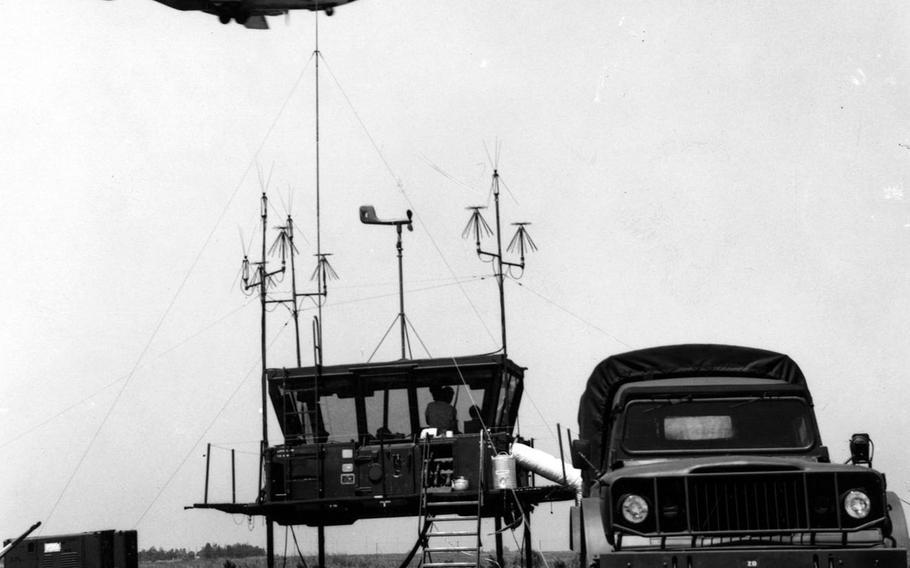 "An aircraft flies by a temporary control tower that servicemembers called ""the mini-van"" at Ching Chuan Kang Air Base, Taiwan, in May 1969."