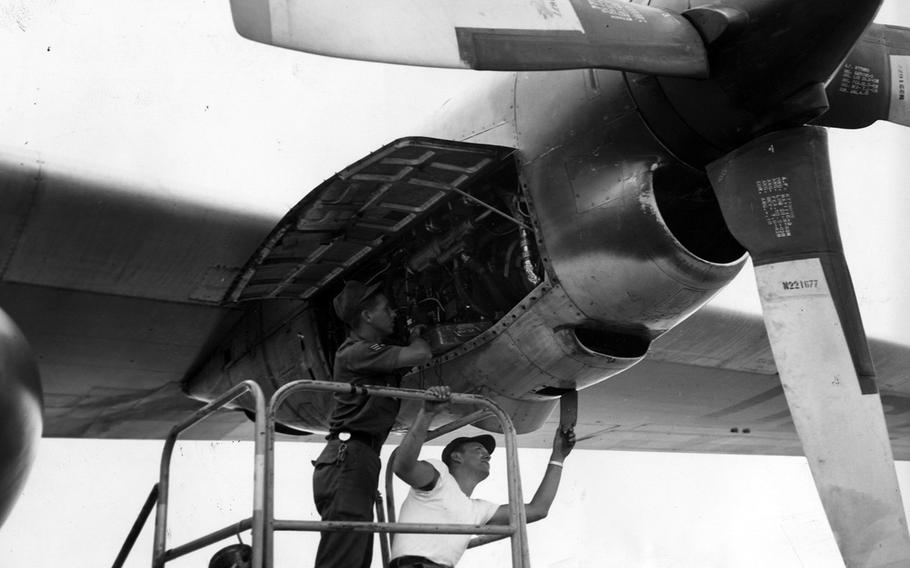 A pair of airmen check for oil leaks on an aircraft in August 1966 at Ching Chuan Kang Air Base, Taiwan.