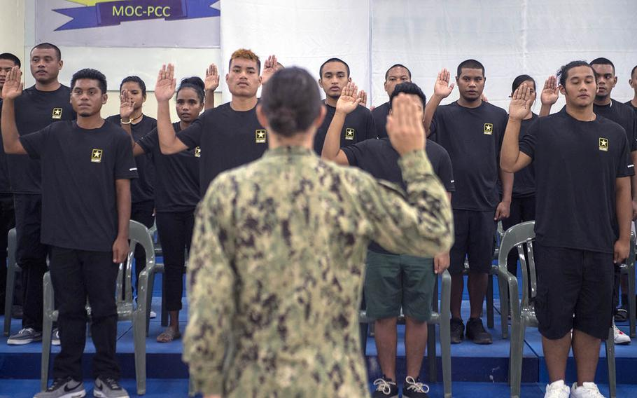 Lt. Cmdr. Gina Becker, commander of Honolulu Military Entrance Processing Station, administers the enlistment oath to enlistees in Koror, Palau, on July 20, 2018.