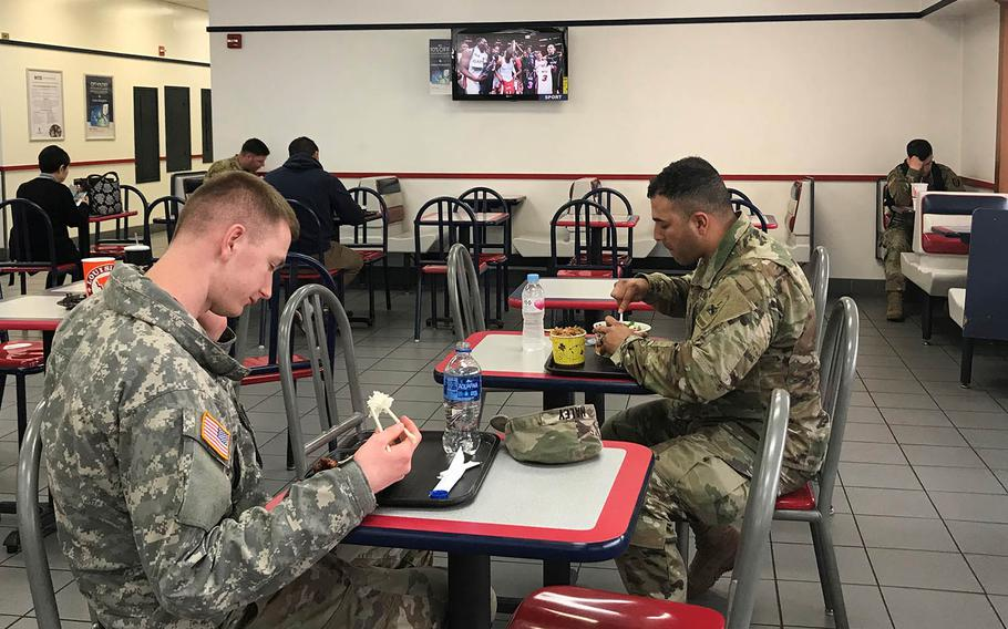 Soldiers eat lunch at the U.S. Army Garrison Yongsan food court while a TV shows sports programming Wednesday, April 10, 2019.