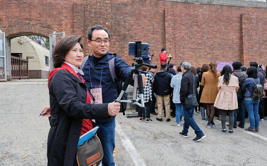 South Korean visitors take a selfie outside the gates of a historic Japanese military stockade located inside Yongsan Garrison, South Korea, on Tuesday, April 9, 2019.