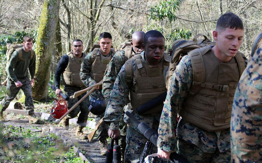 Marines tote their gear for the Marine Corps Martial Arts Instructor course at Combined Arms Training Center Camp Fuji, Gotemba, Japan, on Wednesday, April 10, 2019.
