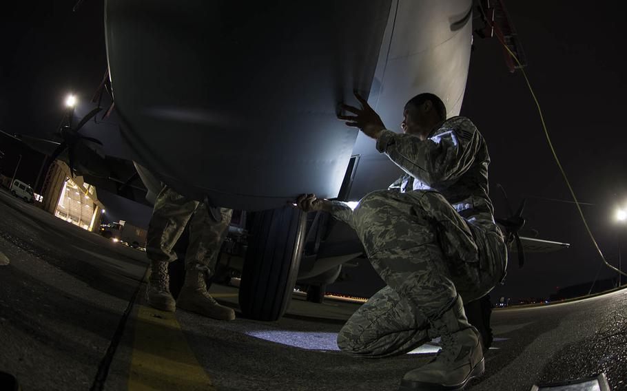 Staff Sgt. Alexander Young holds a panel on a C-130J Super Hercules as Senior Airman Mark Kelly prepares the aircraft for a wash at Yokota Air Base, Japan, on March 21, 2019.