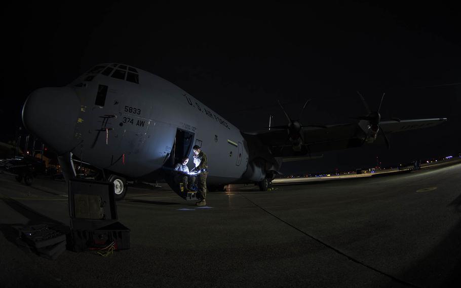 Airman 1st Class Alice Merrill and Senior Airman Mark Kelly review preparations for washing a C-130J Super Hercules at Yokota Air Base, Japan, on March 21, 2019.