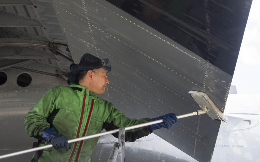 Sugi Yama, a contractor at Yokota Air Base, Japan, washes a C-130J Super Hercules on March 21, 2019.