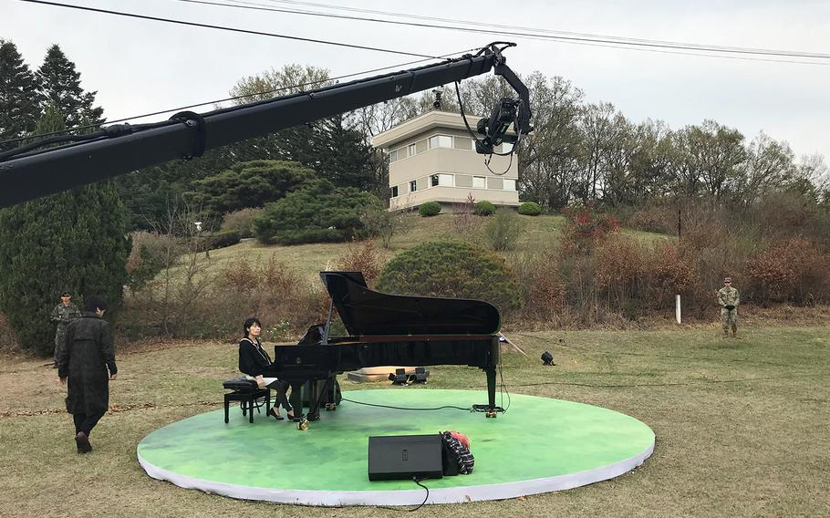 A pianist performs near the pine tree planted by South Korean President Moon Jae-in and North Korean leader Kim Jong Un in the truce village of Panmunjom, Saturday, April 27, 2019.