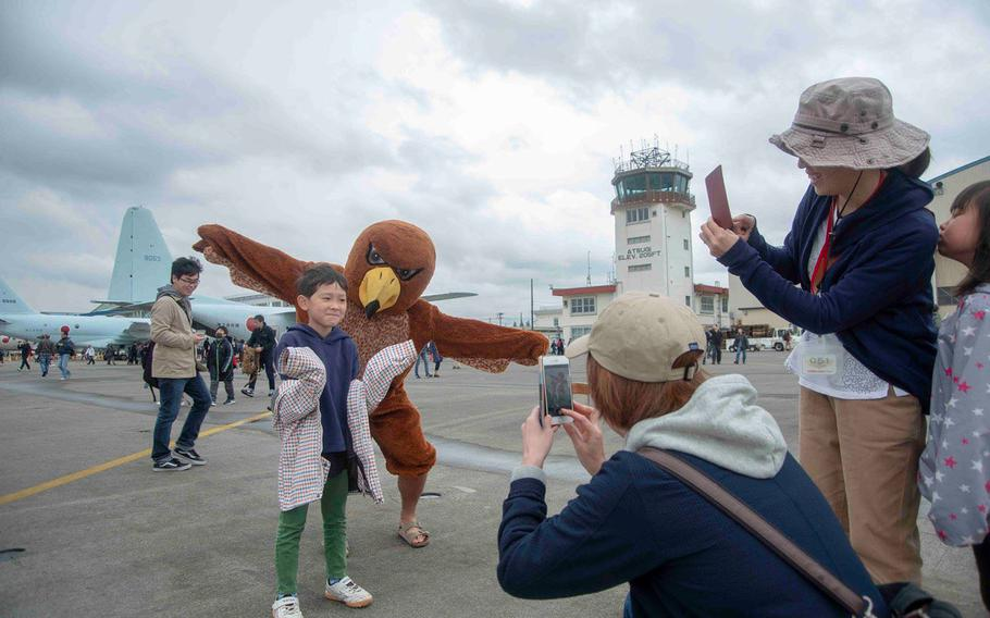 A mascot for Helicopter Maritime Strike Squadron 77 poses with a guest during the Spring Festival at Naval Air Facility Atsugi, Japan, Saturday, April 27, 2019.
