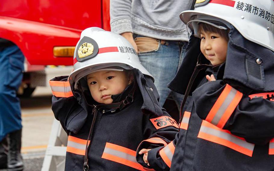 Children try on Japanese firefighter gear during the Spring Festival at Naval Air Facility Atsugi, Japan, Saturday, April 27, 2019.