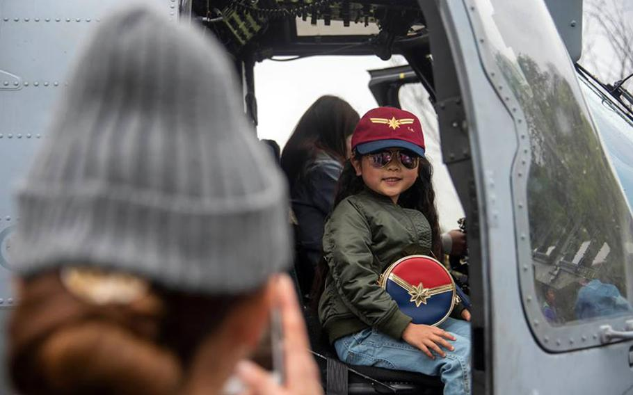 A child poses aboard a U.S. military aircraft during the annual Spring Festival at Naval Air Facility Atsugi, Japan, Saturday, April 27, 2019.