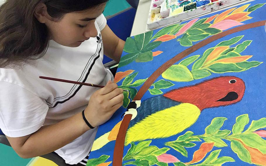"""Constance Jones, a senior at Zama American High School in Japan, works on a painting called """"Bird on Branch,"""" during the Far East Film and Creative Expressions Festival in Tokyo, May 2, 2019."""