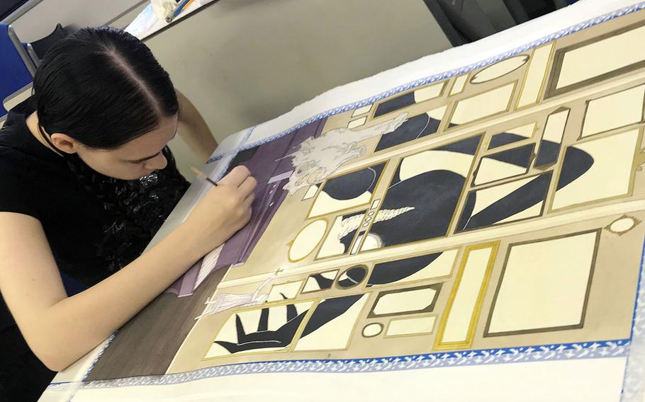 """Meaghan Nelson, a junior at Yokota High School in Japan, works on her award-winning painting, """"What Lurks in the Shadows,"""" during the Far East Film and Creative Expressions Festival in Tokyo, May 2, 2019."""