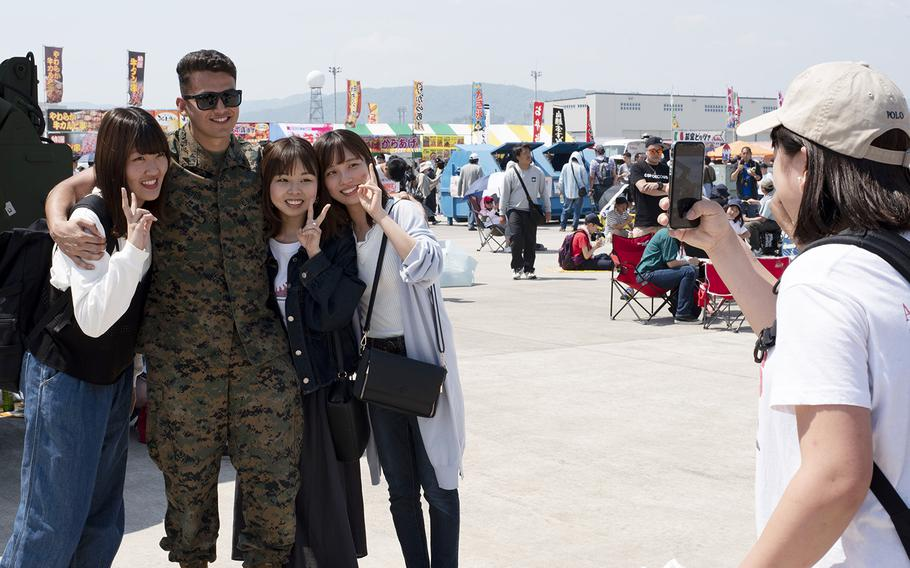 A Marine poses with visitors during the Friendship Day 2019 at Marine Corps Air Station Iwakuni, Japan, Sunday, May 5, 2019.