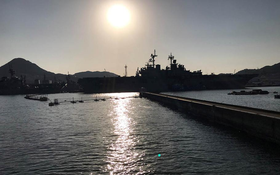 Ships, including the USS Wasp, are seen in silhouette at Sasebo Naval Base, Japan, in March 2019.