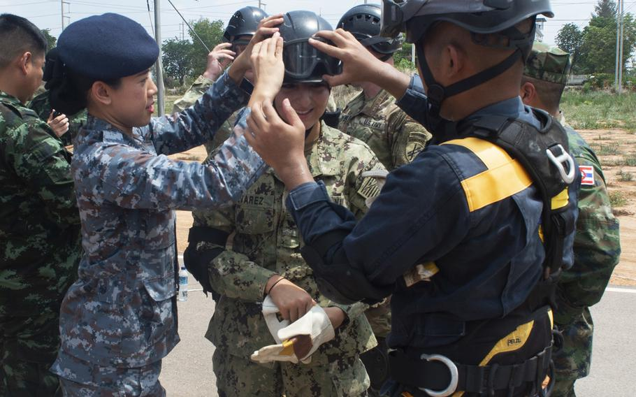 Members of the Thai Royal Armed Forces assist Petty Officer 3rd Class Sandra Alvarez, assigned to Pacific Partnership 2019, with her protective gear during a humanitarian-assistance and disaster-relief demonstration in Chachoengsao province, Thailand, May 23, 2019.