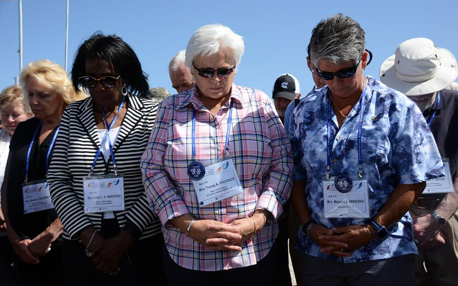 Annie Winstead, Tracey Province and Melanie Mikeska join other relatives of missing American servicemembers in a moment of silence, May 29, 2019, during a visit to the Korean War battleground known as Arrowhead Hill for a rare view of the site in the Demilitarized Zone where South Korea is excavating for remains.