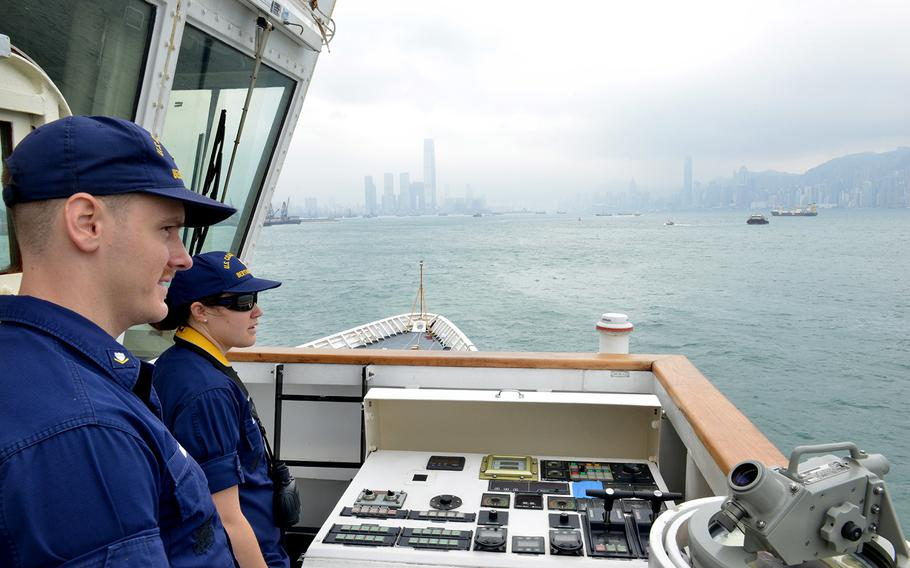 Petty Officer 3rd Class Brendan Hoban and Ensign Cristina Sandstedt monitor vessel traffic as the Coast Guard cutter Bertholf approaches Hong Kong, April 15, 2019.