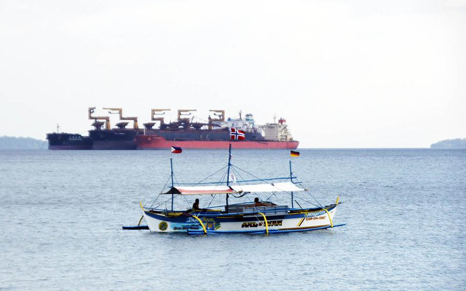A tourist boat drifts in front of a commercial vessel near Baloy Beach in Subic Bay, Philippines, in March 2015.