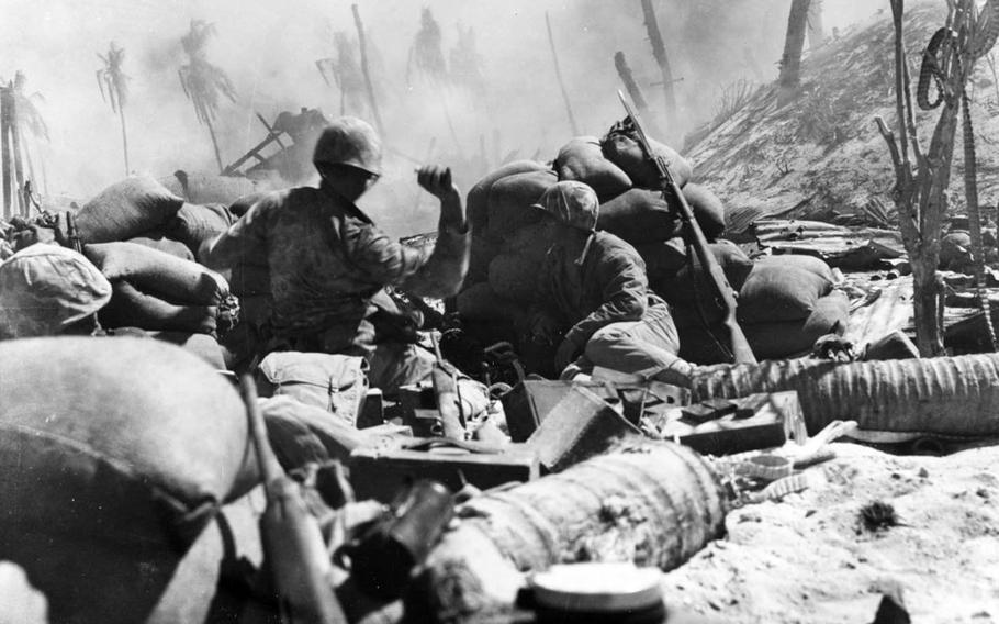 A U.S. Marine throws a grenade on Betio Island during World War II's Battle of Tarawa in November 1943.