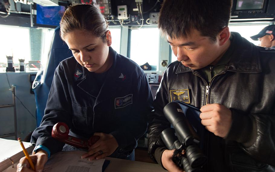 Petty Officer 2nd Class Diana Espinoza communicates ship movements with a South Korean navy sailor during Foal Eagle 2017.