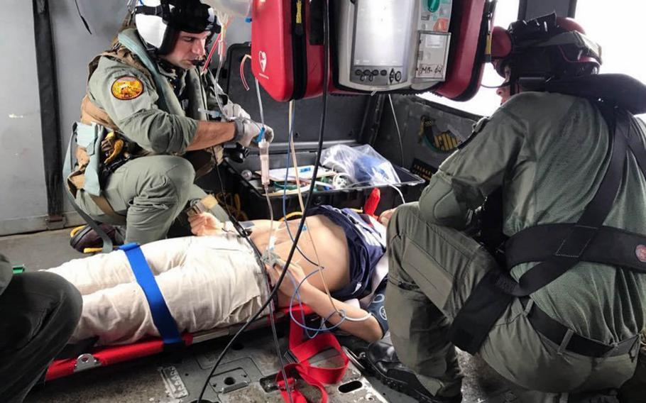 Lt. Erik Kumetz and Petty Officer 2nd Class Kyle Bowen of Helicopter Sea Combat Squadron 25, Guam, provide medical care to a Chinese mariner on Tuesday, Aug. 6, 2019.