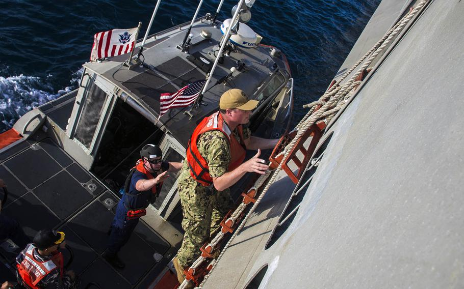 Lt. Ben Ralen of Destroyer Squadron 7 climbs aboard the USS Montgomery during a passenger transfer as part of Cooperation Afloat Readiness and Training Indonesia 2019 on Aug. 5, 2019.
