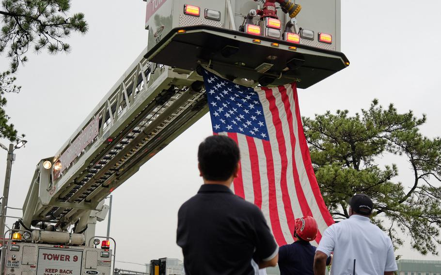 Firefighters prepare to hoist an American flag during the ninth annual 9/11 Memorial Ruck March at Camp Humphreys, South Korea, Wednesday, Sept. 11, 2019.