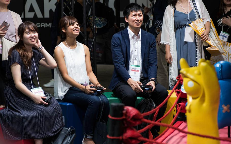 Attendees of the Tokyo Game Show 2019 play a game at an indie game development booth on Thursday, Sept. 12, 2019.