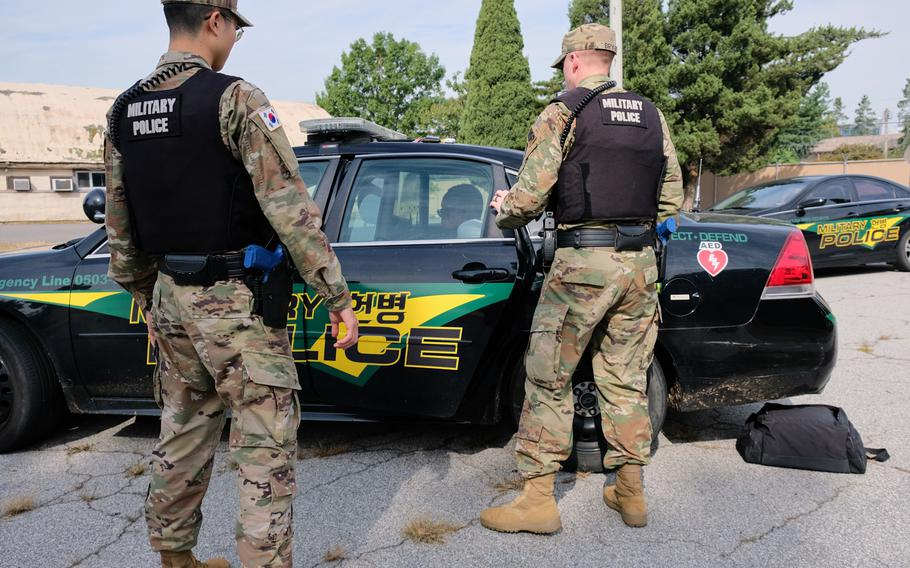 Soldiers from the 142nd Military Police Company place a servicemember role-playing a suspect into a cruiser during a training exercise at Yongsan Garrison, South Korea, on Thursday, Sept. 26, 2019.