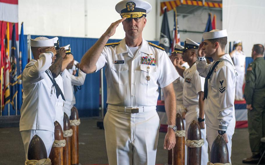 Rear Adm. George M. Wikoff exits the stage after taking command of Task Force 70 aboard the USS Ronald Reagan in the South China Sea on Sunday, Sept. 29, 2019.