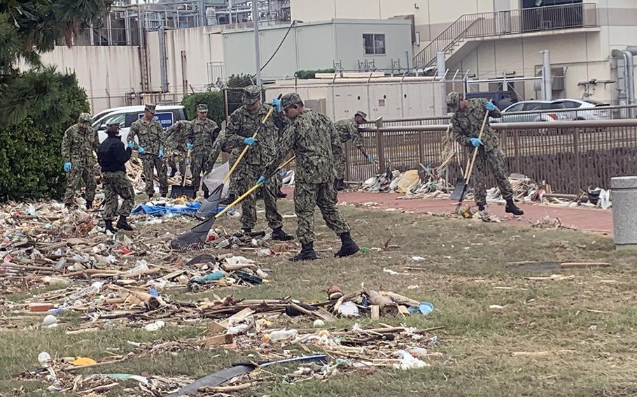 Sailors rake debris at Yokosuka Naval Base, Japan, Tuesday, Oct. 15, 2019, days after deadly Typhoon Hagibis ripped through the area.
