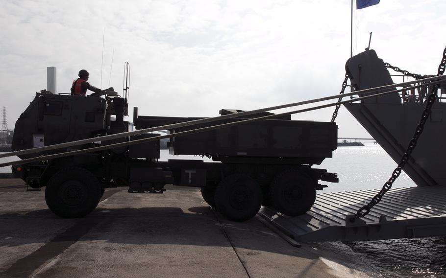 A member of the 12th Marine Regiment HIMARS platoon backs a launcher onto an Army vessel at Kin, Okinawa, Thursday, Oct. 31, 2019.