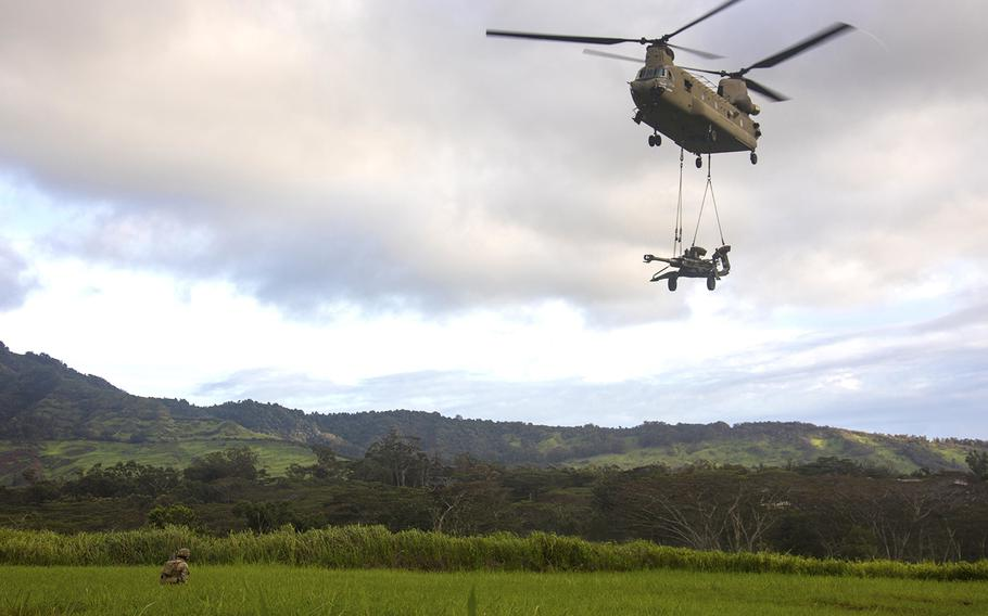A CH-47 Chinook helicopter transports a howitzer over a range at Schofield Barracks, Hawaii, Oct. 10, 2019.