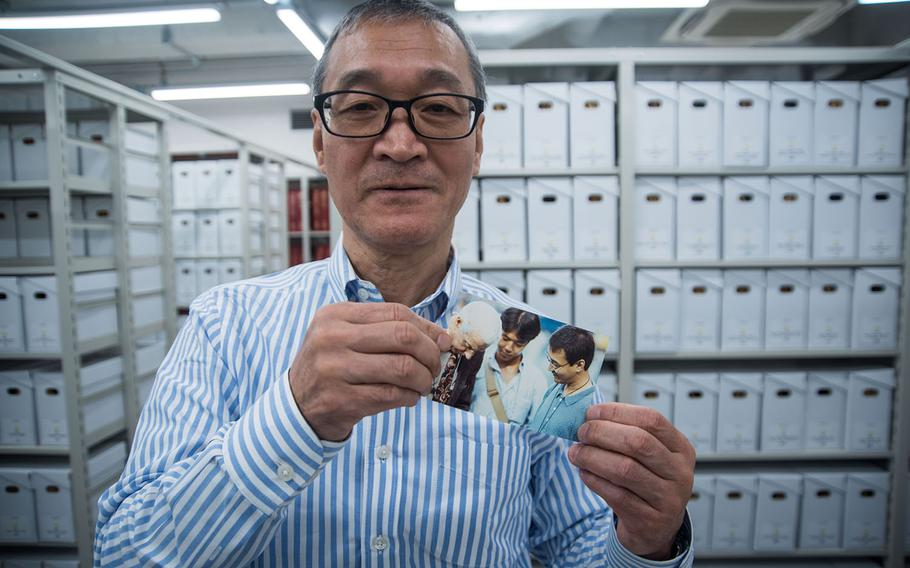 Stars and Stripes librarian Norio Muroi holds a photo of himself, far right, meeting Yankees legend Joe DiMaggio during a reporting assignment in Tokyo in the early 1990s.