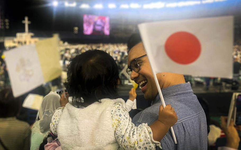 Lt. Cmdr. Ryan de Vera, a public affairs officer at Yokosuka Naval Base, Japan, holds his 1-year-old daughter, Avery, as they wait to see Pope Francis at the Tokyo Dome on Monday, Nov. 25, 2019.
