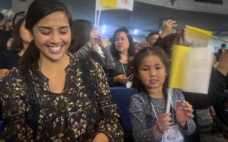 Navy spouse Joy de Vera, 35, laughs as her daughter Riley, 4, waves a Vatican flag before Pope Francis' visit to the Tokyo Dome, Japan, on Monday, Nov. 25, 2019.