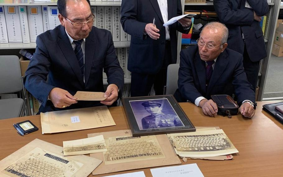 Akitaka Nagasawa, left, shows photographs of his uncle Yoshio Nagasawa, whose portrait in uniform is at center. Yoshio Nagasawa's World War II-era flag was returned to his family in Japan on Monday, Nov. 25, 2019.