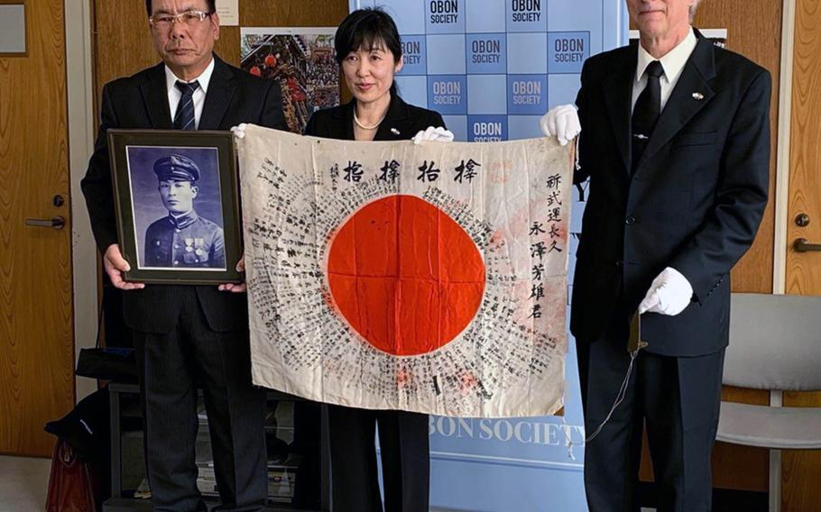 A Japanese flag carried in World War II by Yoshio Nagasawa was returned to his nephew Akitaka Nagasawa, left, in Japan by Keiko Ziak and Rex Ziak of the Obon Society on Monday. Nov. 25, 2019.