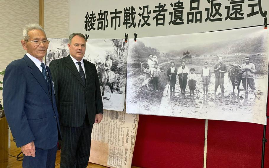 Tamotsu Shikata, left, and Jarat Chopra stand before a photograph of Shikata and his family carried by his brother Hideo Shikata during World War II. Chopra returned an album of his brother's photographs to Shikata in Ayabe, Japan, on Sunday, Nov. 24, 2019.
