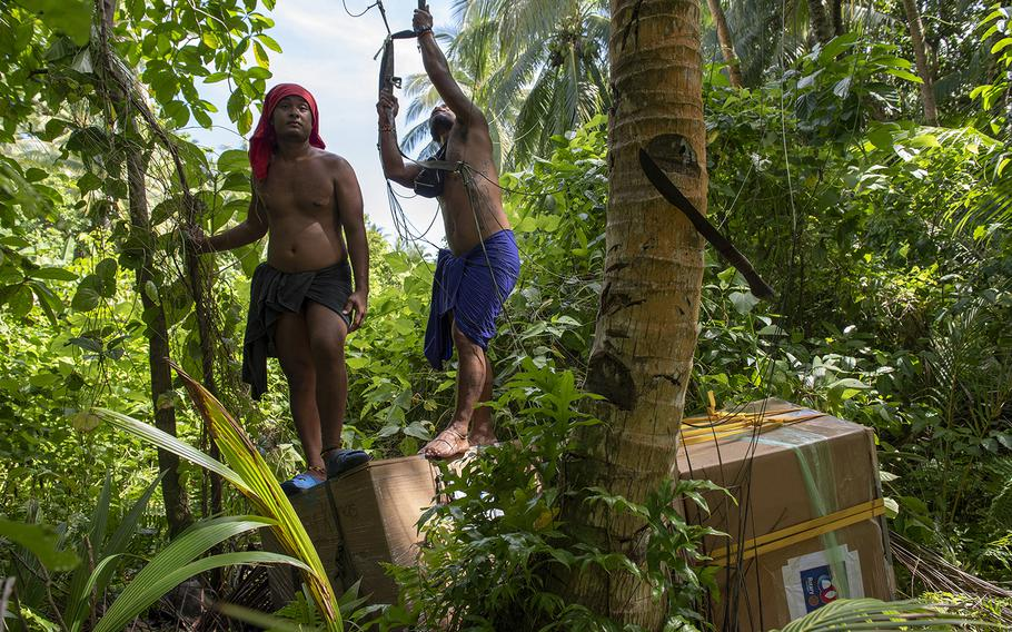 Villagers stand atop humanitarian aid bundles airdropped to the island of Woleai, Micronesia, during Operation Christmas Drop, Tuesday, Dec. 10, 2019.