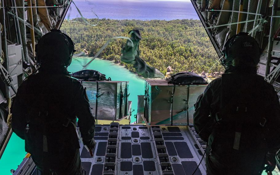 Cpl. Toni Thompson, right, and Sgt. Ethan Moran of the Royal New Zealand Air Force send supplies to a Micronesian island during Operation Christmas Drop, Wednesday, Dec. 11, 2019.