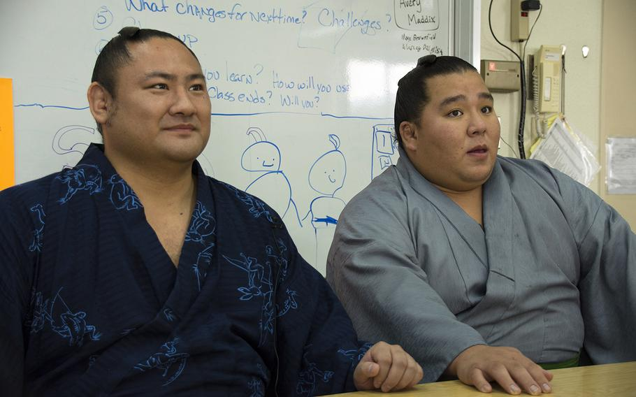 Japanese sumo wrestlers Kotoeko, left, and Kotooodutsu answer questions at Lester Middle School at Camp Lester, Okinawa, Friday, Dec. 13, 2019.