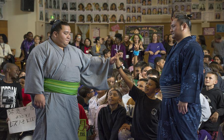 Sumo wrestler Kotoeko, right, watches as Kotooodutsu high-fives a Lester Middle School student at Camp Lester, Okinawa, Friday, Dec. 13, 2019.
