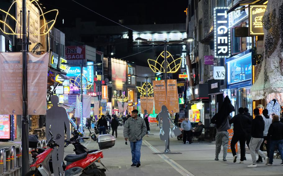 Service members and locals walk through an entertainment district just outside Osan Air Base, South Korea, on Saturday, Dec. 14, 2019.