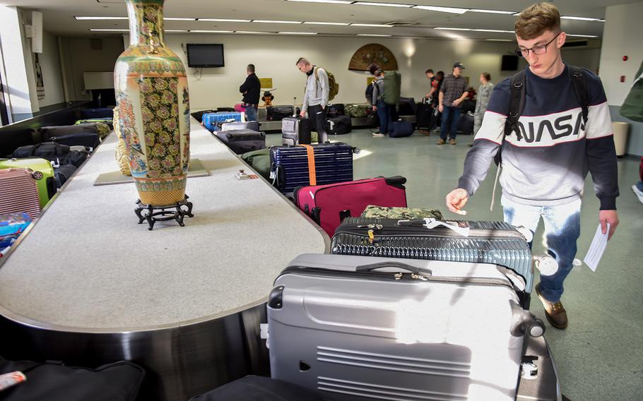 Patriot Express passengers wait for their luggage inside the passenger terminal at Yokota Air Base, Japan, in 2018.