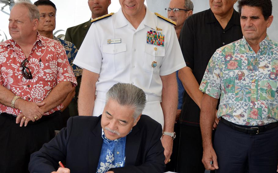 Hawaii Gov. David Ige signs a proclamation while seated on the deck of the Battleship Missouri Memorial, Wednesday, Dec. 18, 2019, announcing the membership of the committee overseeing next year's 75th anniversary of the end of World War II. Ige and U.S. Indo-Pacific Command head Adm. Phil Davidson, standing behind the governor, are honorary committee co-chairs.