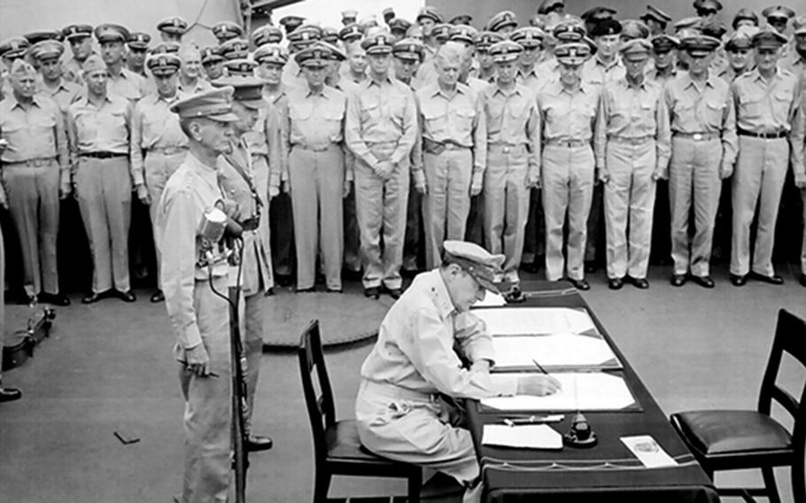 Allied sailors and officers watch Gen. Douglas MacArthur sign documents during the surrender ceremony aboard USS Missouri that ended World War II on Sept. 2, 1945.