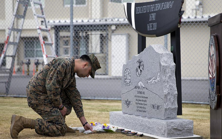 Marine Corps Sgt. Alberto Ruiz, a loadmaster with Marine Aerial Refueler Transport Squadron 152, lays flowers during the unveiling of a memorial at Marine Corps Air Station Iwakuni, Japan, Dec. 5, 2019. The memorial honors five Marine aviators killed last year in a midair collision off Japan.