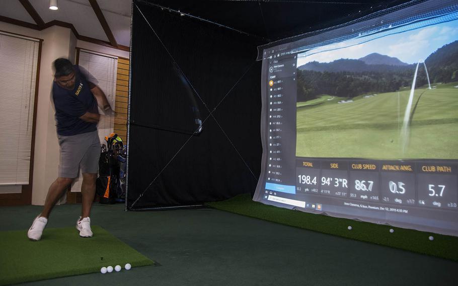 Navy Capt. Jose Cisneros practices his golf swing at a new simulator at the Par 3 Golf Course, Yokota Air Base, Tokyo, Japan, on Dec. 13, 2019.
