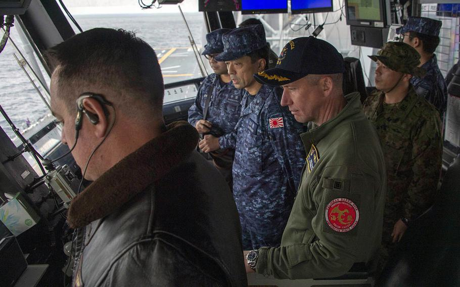 Capt. Luke Frost, center, commander of amphibious assault ship USS America, and Japan Maritime Self-Defense Force Rear Adm. Shirane Tsutomu, commander, JMSDF Mine Warfare Force, watch flight operations in America's primary flight control center in the East China Sea on Jan. 13, 2020.